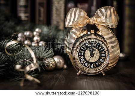 Vintage alarm clock in traditional study room showing five to midnight. Happy New Year! - stock photo