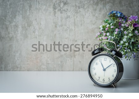 Vintage alarm clock on a night table with flowers - stock photo