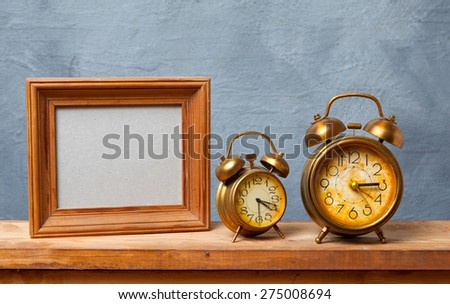 Vintage alarm clock on the table with photo frame - stock photo