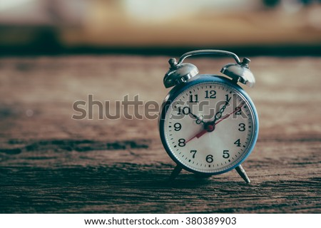 Vintage alarm clock on weathered wood background