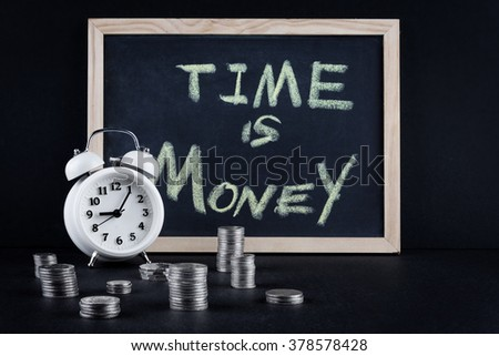 """Vintage alarm clock showing 5 o'clock and coin towers with chalckboard and """"time is money"""" text on black background. - stock photo"""