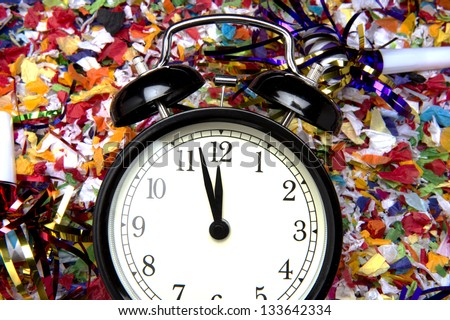 Vintage alarm clock sitting on confetti with hands about to strike midnight - stock photo