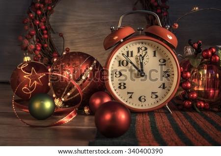 Vintage alarm clock snowing five to twelve and seasonal decorations. Happy New Year 2016! - stock photo