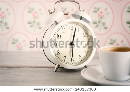 Vintage alarm clock with cup of coffee on wooden background - stock photo