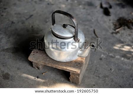 vintage aluminium kettle on small wooden chair - stock photo