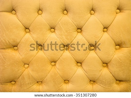 Vintage amber leather upholstery buttoned sofa (background) - stock photo