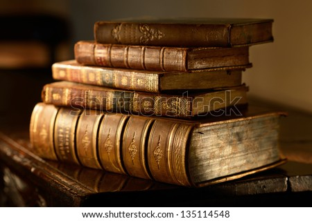 Vintage, antiquarian  books pile on wooden surface in warm directional light. Selective focus. - stock photo