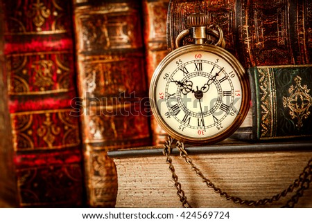 Vintage Antique pocket watch on the background of old books - stock photo