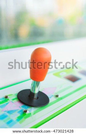 Vintage arcade video game joystick in amusement park, selective focus