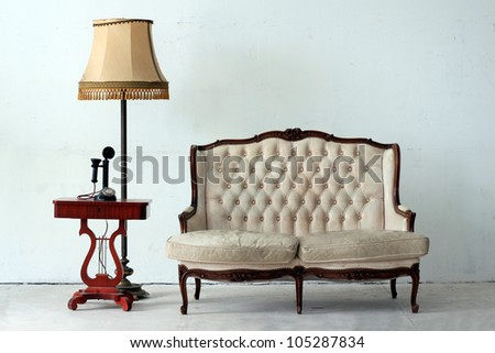 Vintage armchair with retro lamp and old day telephone - stock photo