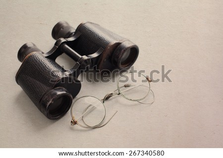 Vintage army binocular and glasses. aged paper background - stock photo