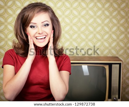 vintage art portrait of young smiling woman looking out at camera in room with wallpaper and tv set from 70s, retro stylization, toned - stock photo