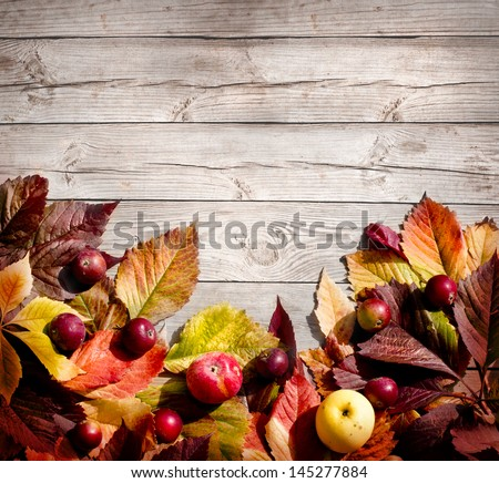 Vintage Autumn border from apples and fallen leaves on old wooden table/Thanksgiving day concept/background with apples - stock photo