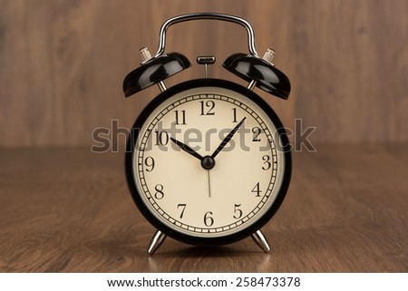Vintage background with alarm clock on a table - stock photo