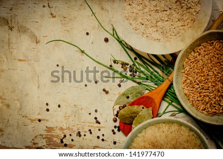 Vintage background with bowls of rice and spices,fresh herbs,with  green spring onions,bay leafs - stock photo
