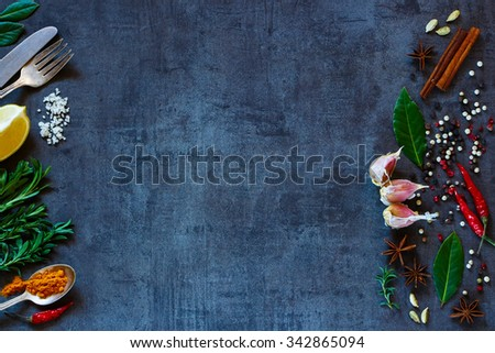 Vintage background with bright spices and space for text. Herbs and spices selection. Healthy eating and cooking concept. Top view. Dark rustic style. - stock photo