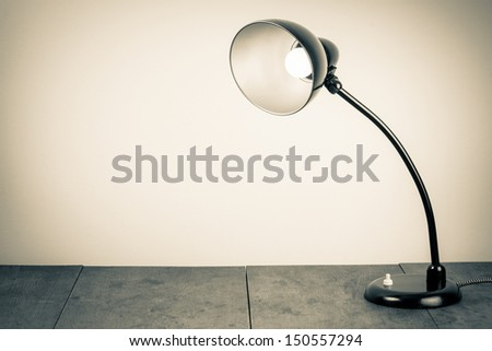 Vintage background with lighting retro desk lamp on wood table - stock photo
