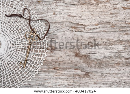 Vintage background with old key and lace on the rude wood - stock photo