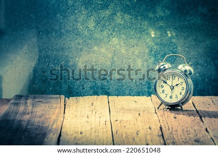 Vintage background with retro alarm clock on table. - stock photo
