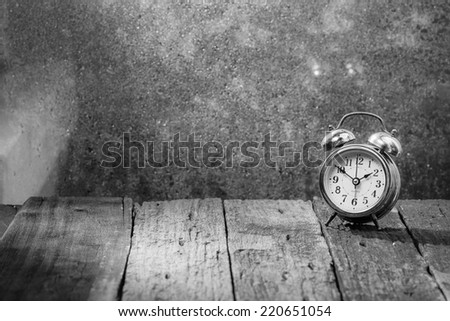 Vintage background with retro alarm clock on table,black and white - stock photo