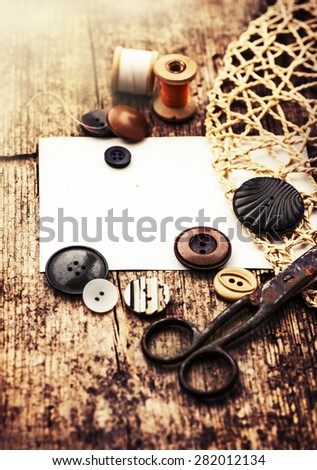 Vintage Background with sewing/Sewing kit. Scissors,, buttons bobbins with thread and needles on the old wooden background - stock photo