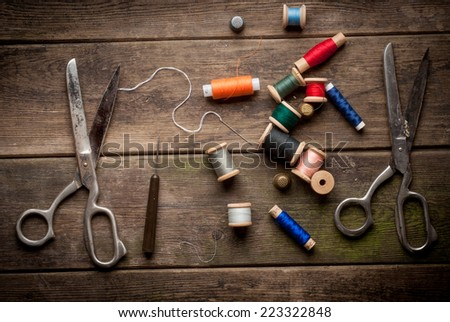 Vintage Background with sewing tools and colored tape. Sewing kit. Scissors, bobbins with thread and needles on the old table. - stock photo