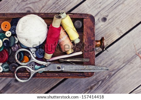 Vintage Background with sewing tools and colored tape/Sewing kit. Scissors, bobbins with thread and needles on the old wooden background