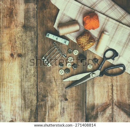 Vintage Background with sewing tools and sewing kit over wooden textured background  - stock photo