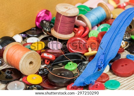 Vintage background with sewing tools and sewing kit. Scissors, bobbins, buttons on the old wooden background.
