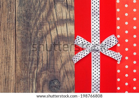 vintage background with wood, polka dot paper and red and white polka dot ribbon with bow - stock photo