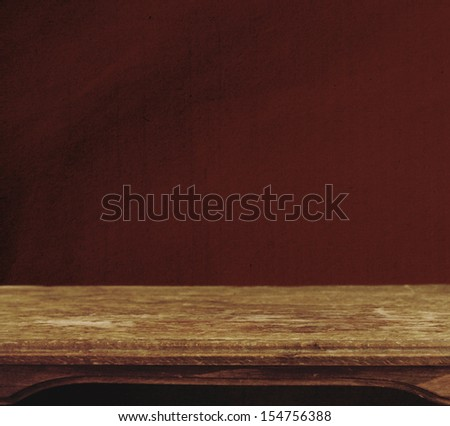 Vintage background with wooden table and grunge red wall - stock photo