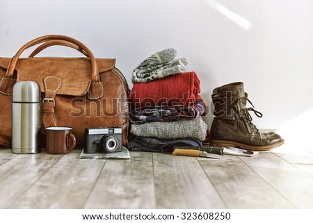 vintage bag with clothes and accesoriese for travel - stock photo