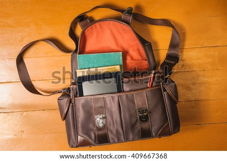 Vintage bag with old books on wood - stock photo