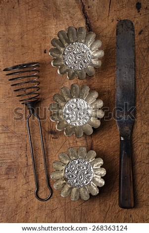 Vintage  Baking utensils - spatula, tins and moulds on wooden board - stock photo