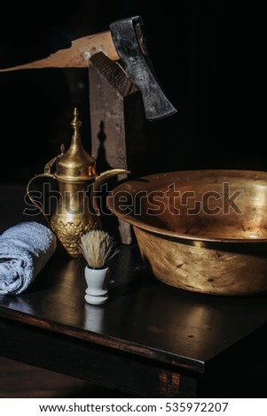 Vintage barber or shaver tools on wooden table. Old copper basin, water jug, axe, shaving brush and towel in barbershop or hairdressing saloon