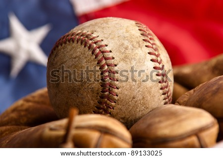 Vintage baseball and glove with American flag in the background