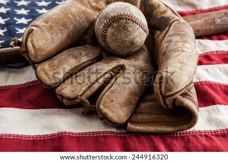 Vintage baseball, glove and bat on an American flag - stock photo