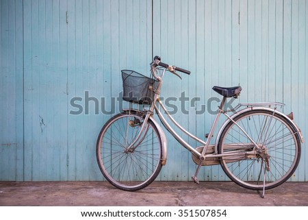 Vintage basket bicycle with old blue wooden wall background - stock photo