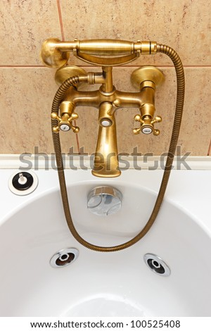 Vintage bathtub faucet and ceramic tiles in background.Bathtub with jacuzzi.Retro bronze look. - stock photo