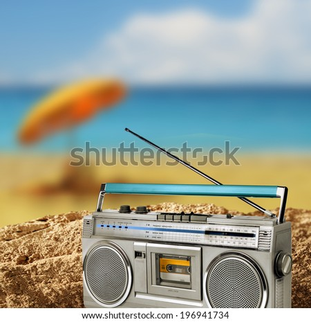Vintage beach gear on sandy beach by blue sea, holiday concept - stock photo