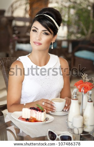 vintage beautiful woman in restaurant cafe with tiramisu cake and coffee.Healthy food  drink for breakfast.Stylish rich slim girl in retro dress.glamorous lady at vacation. Retro style.France.series - stock photo