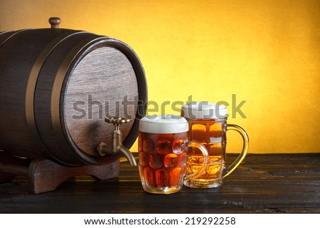 Vintage beer barrel with two beer glasses on wooden table still life with copy space