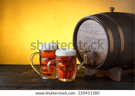 Vintage beer barrel with two beer glasses on wooden table still life with copy space - stock photo