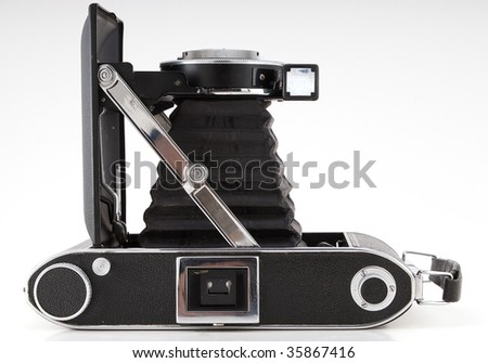 Vintage bellows camera isolated against a white background