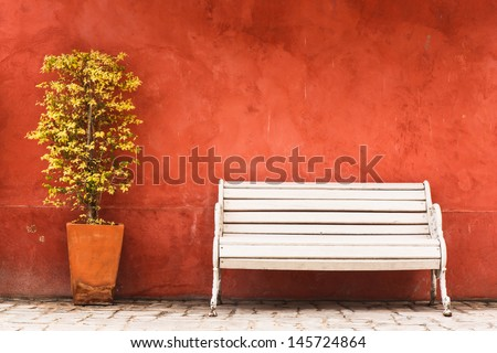 Vintage Bench and tree against blank wall - stock photo