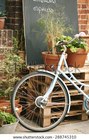 Vintage bicycle in front of chalk board sign of trendy London cafe