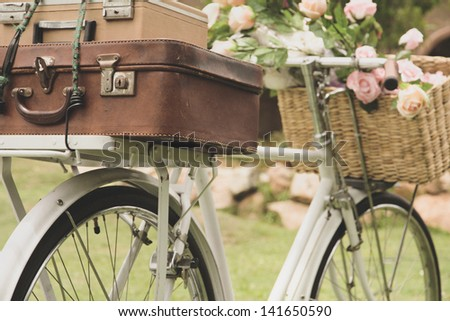 Vintage bicycle on the field with a bag and basket - stock photo