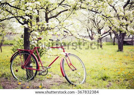 Vintage bicycle waiting near tree against spring nature background - stock photo