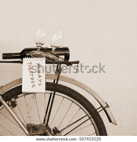 Vintage bicycle with bottle of wine and two glasses at the back. Space for text.