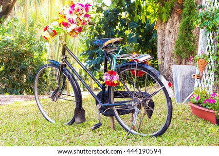 Vintage Bicycle with flowers on summer landscape background